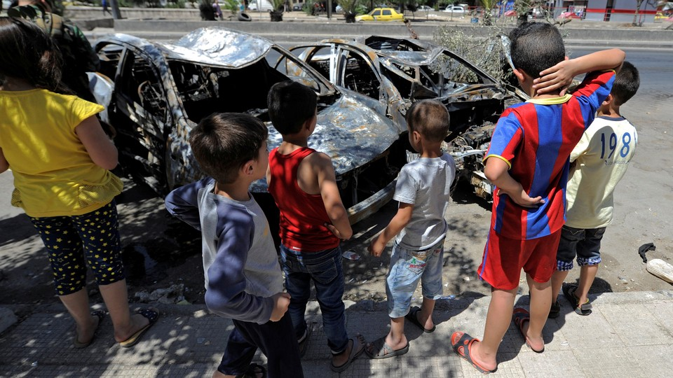 Children look at the wreckage of vehicles at a blast site in the Baytara traffic circle near the Old City of Damascus, Syria.