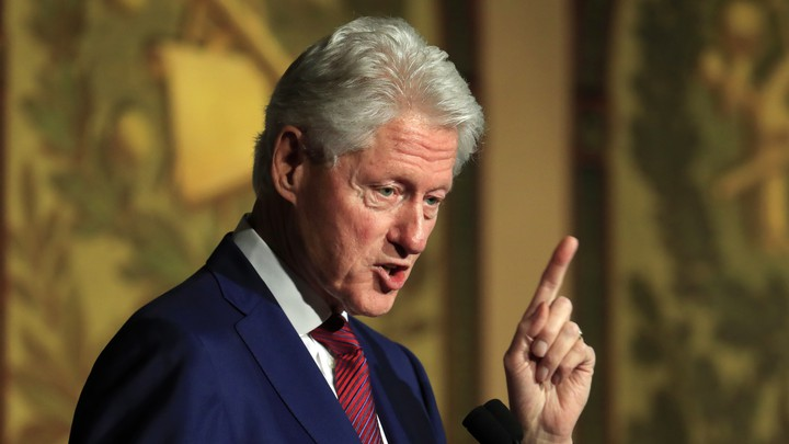 Former President Bill Clinton speaks into a microphone.