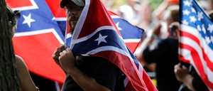 A member of the Ku Klux Klan, wrapped in a Confederate flag, protests in Charlottesville.
