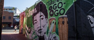 "A colorful mural with a woman's head and words reading ""take me out to the go-go."""