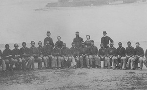 Black Civil War soldiers sitting in a row in front of standing white officers