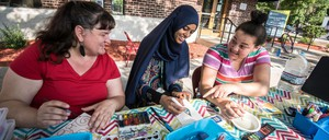 Artist Soozin Hirschmugl paints with two visitors on the lawn of the People's Center Health Services in Minneapolis.