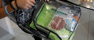 photo: a student displays her clear plastic backpack