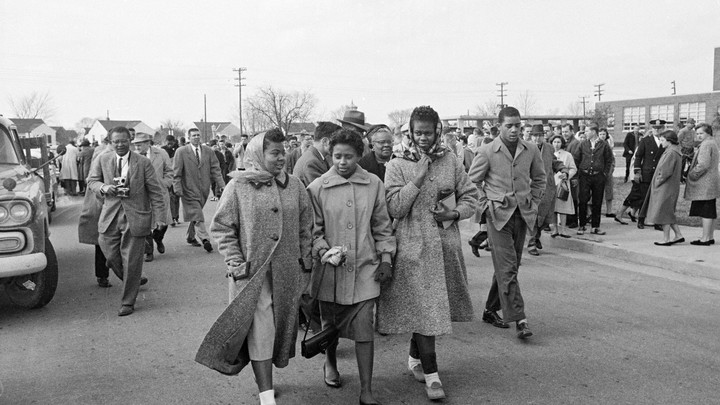 The black and white photos features four black students walking together as white students look on.