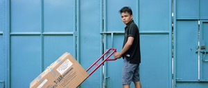A Filipino man pushes a box in a warehouse.