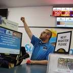 A cashier stands behind the counter at a lottery store.