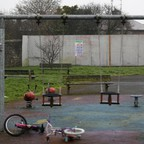 Photograph of a playground with a swing set and bikes, but no kids.