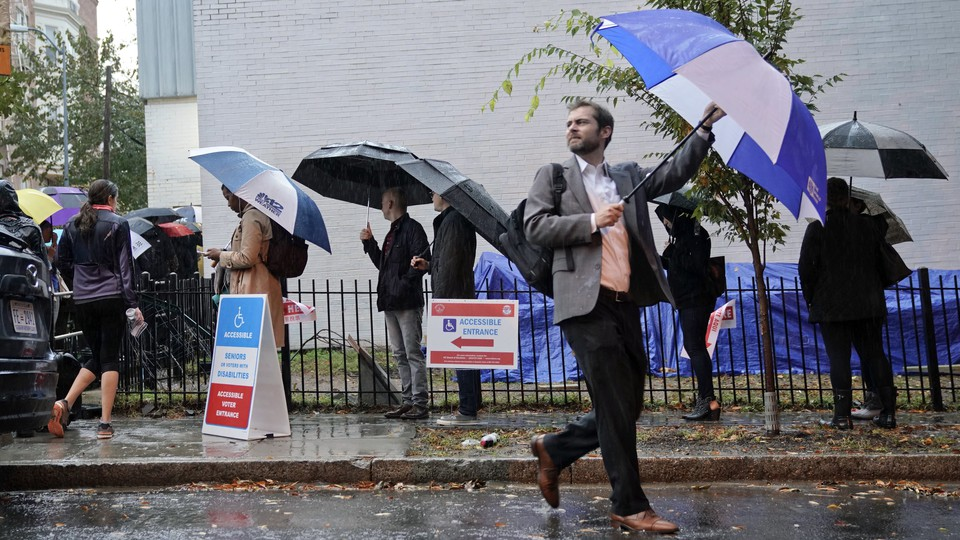 Washington, D.C., voters line up in the rain to cast a ballot in the 2018 midterm elections.