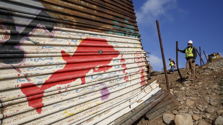 A crew removes part of a border wall near Tijuana, Mexico.