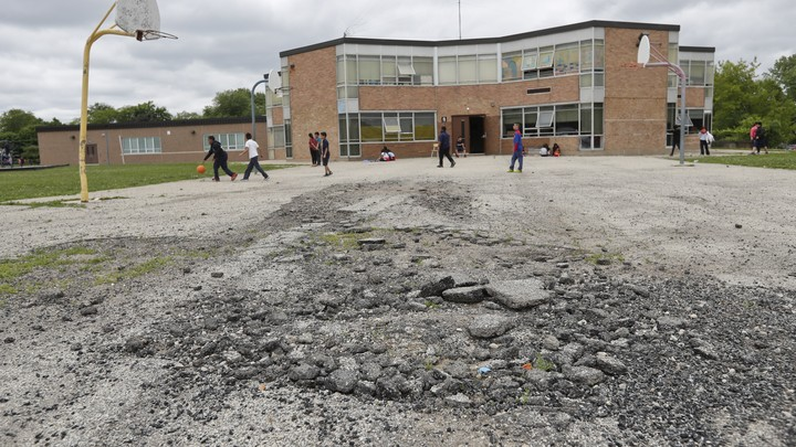 Kids play on a broken basketball court. The net on the hoop is missing. A brick school is in the distance.