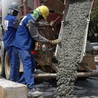 Workers pouring concrete are pictured.