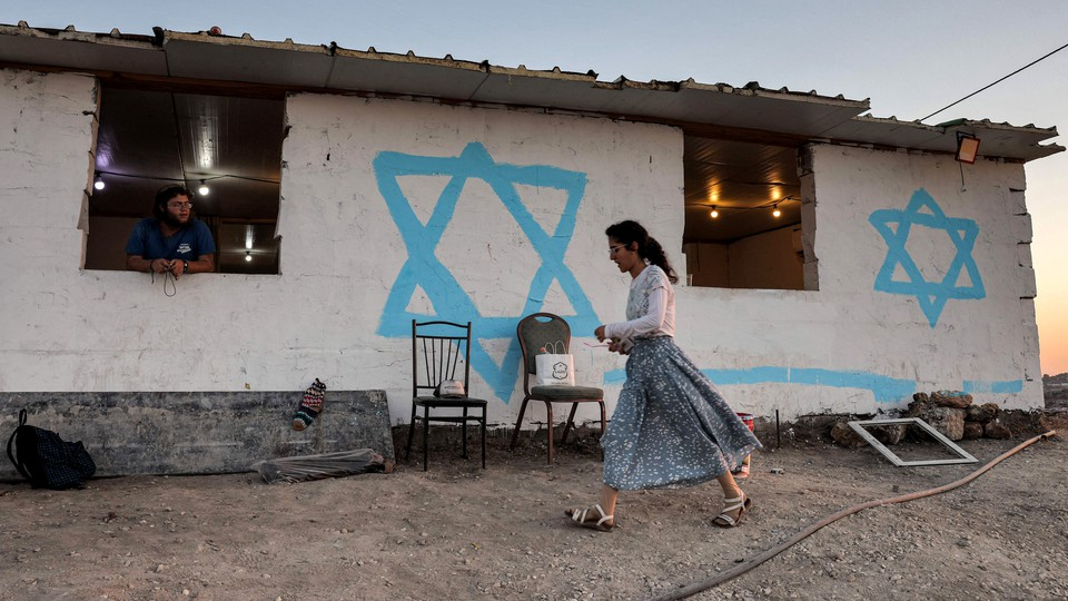 A young woman walks past an Israeli settlers' shack in the newly established wildcat outpost of Eviatar, near the northern Palestinian city of Nablus in the occupied West Bank, on July 1, 2021.