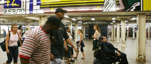 A photo of a wheelchair user in the New York City subway.