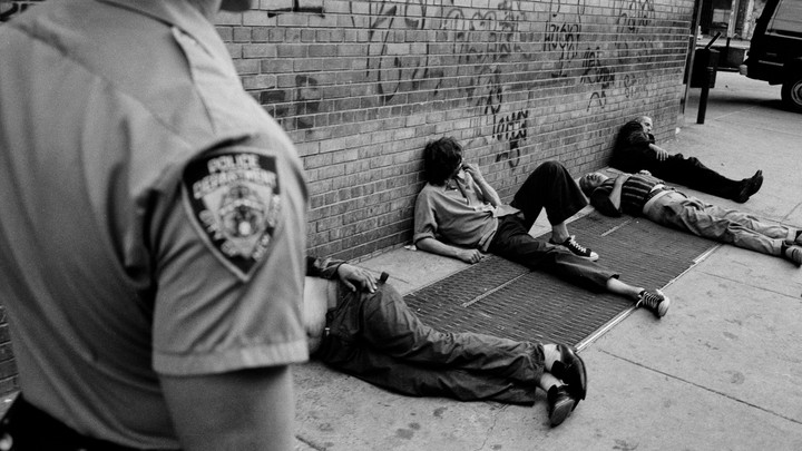 A police officer walking past people lying on the street.