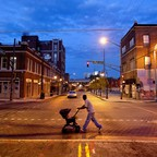 photo: A man pushes a stroller through a crosswalk after dusk in Atlanta, Georgia.