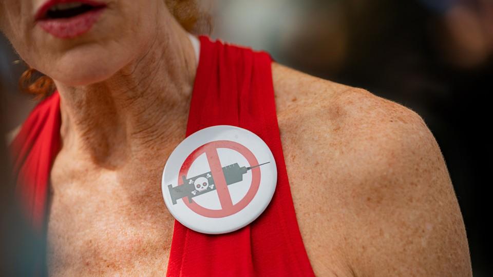 A woman wearing an anti-vax pin.