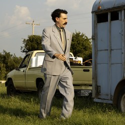 A movie still of Sacha Baron Cohen next to an animal trailer