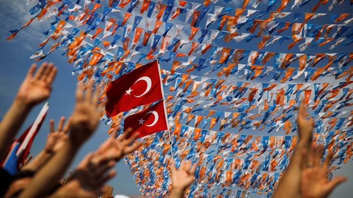 Supporters wave their hands in front of a Turkish flag
