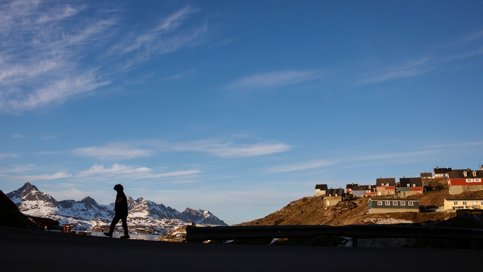 A man walks through Tasiilaq, Greenland.