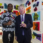 two men in front of colorful paintings