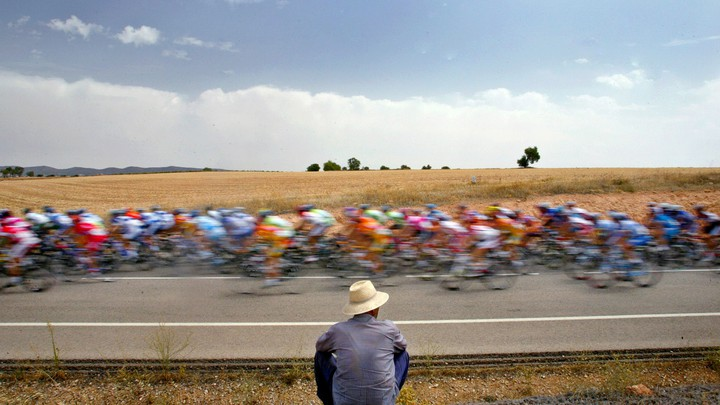 A man looks at a pack of bicyclists during the Tour of Spain in 2005.