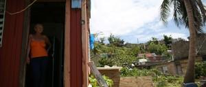 Bexaida Torres stands in the door of what is left of her home after Hurricane Maria hit Puerto Rico.