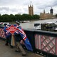 """An anti-Brexit campaigner crosses a bridge opposite Parliament in London holding a """"Stop Brexit"""" sign."""