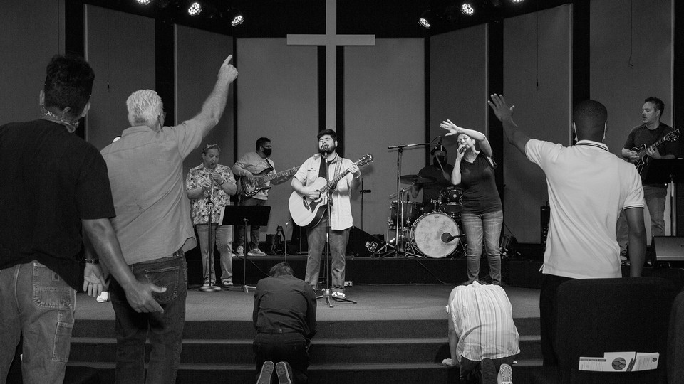 A black-and-white photo of a group standing in a church, listening to someone at the front playing a guitar