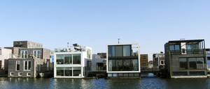 Four houses of wood and glass sit on the water.