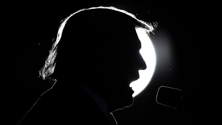 Donald Trump's head silhouetted against a spotlight as he speaks into a microphone