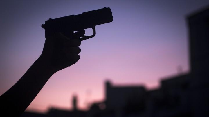 A hand in silhouette holding a shotgun