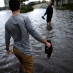 Boys wading through knee-high water on a flooded street after Hurricane Irma