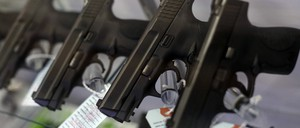 Handguns are seen for sale in a display case.