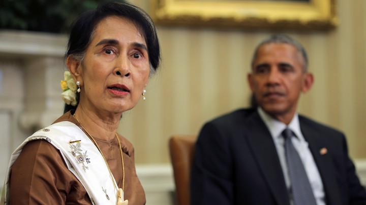 Aung San Suu Kyi looks at the camera while Barack Obama looks at her in the background. They are sitting in the Oval Office.