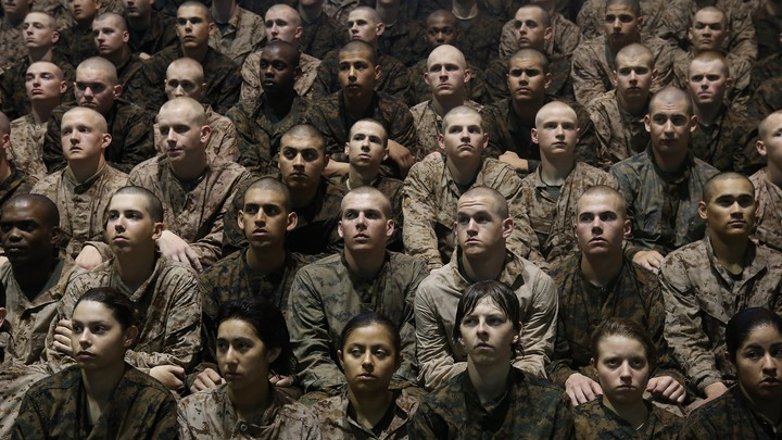 Marine recruits sit in a group listening to a speaker off camera.