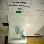 """A water fountain with a """"Do Not Drink Until Further Notice"""" sign posted above it"""