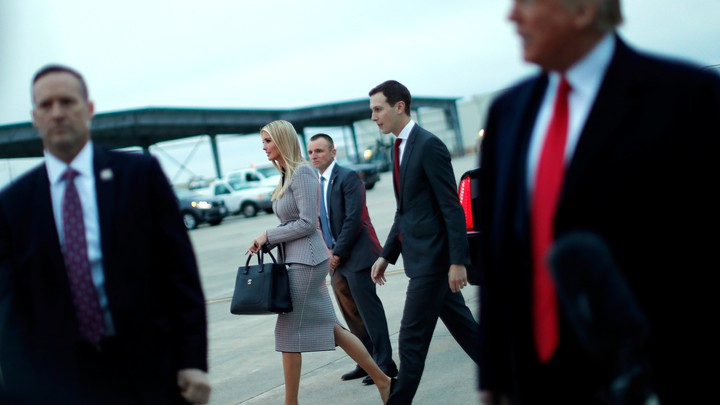 Ivanka Trump and Jared Kushner pass behind Donald Trump.