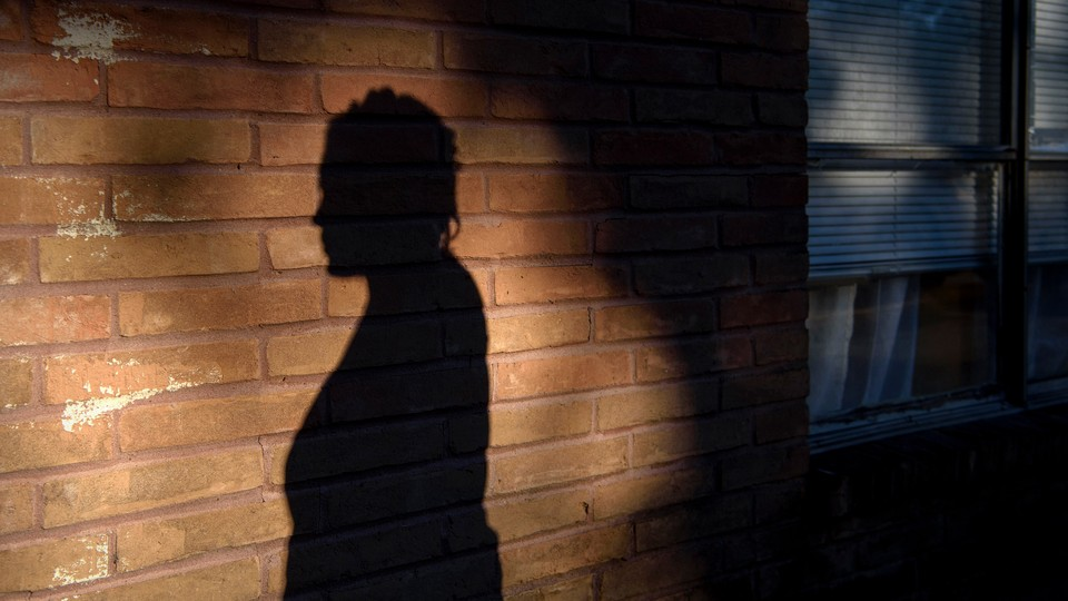 A woman's silhouette on a brick wall