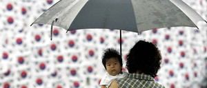A South Korean woman with a baby in her arms in front of Seoul City Hall in 2005.
