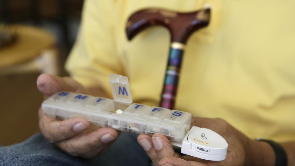 An older person holds a pillbox with sections for days of the week.