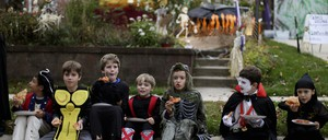 Kids eating pizza in costume on Halloween.
