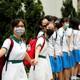 Secondary-school students wearing face masks hold hands, forming a long human chain.