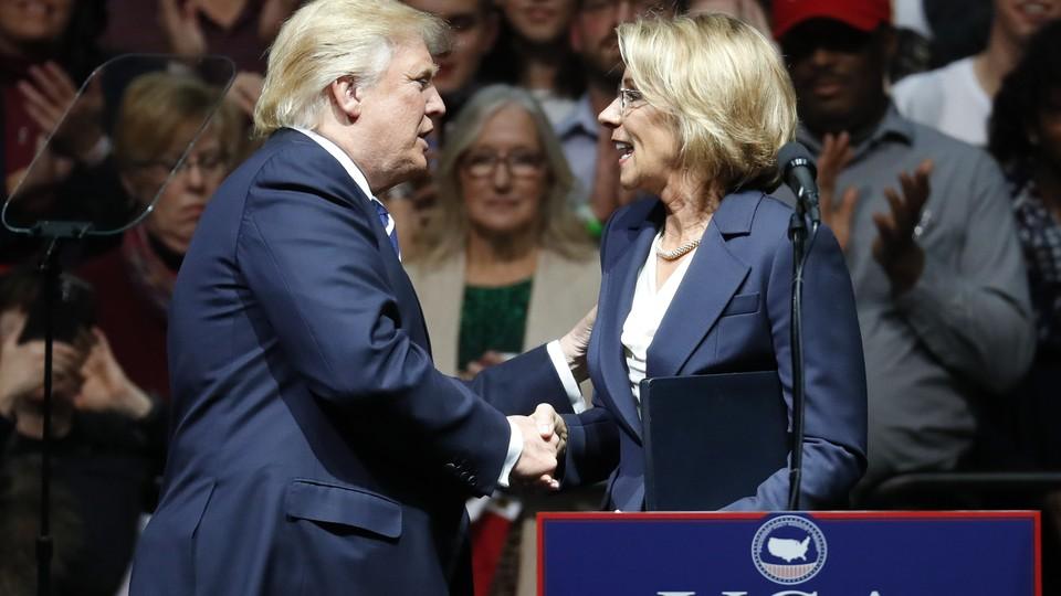 Betsy DeVos and Donald Trump shake hands