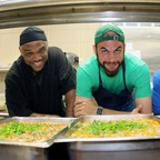 Three men stand behind trays of food in a school cafeteria.