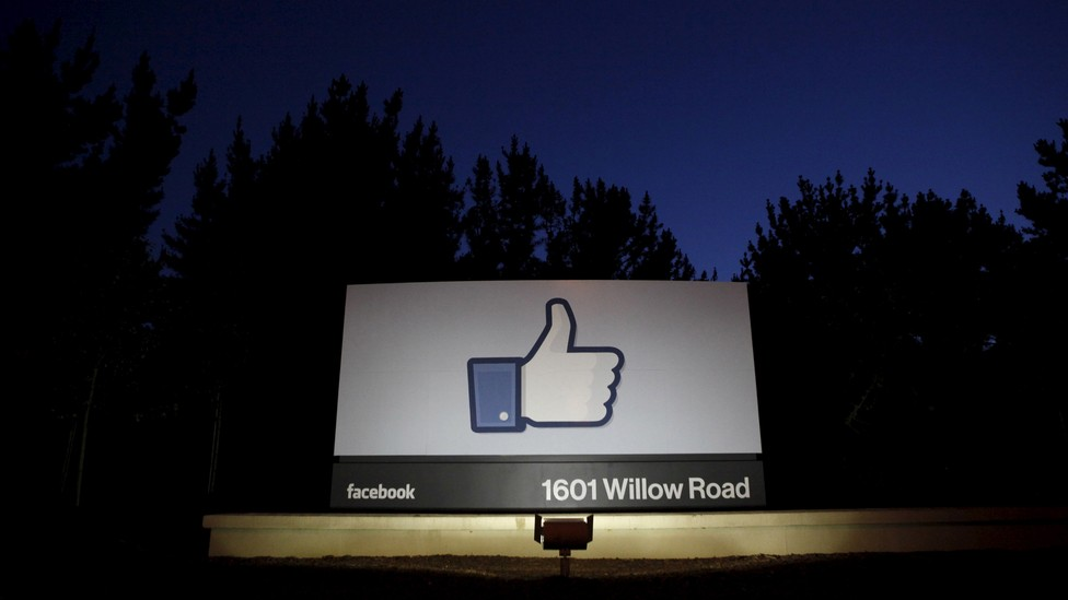 """A Facebook """"like"""" symbol illuminated at night on a sign that says """"1601 Willow Road"""""""