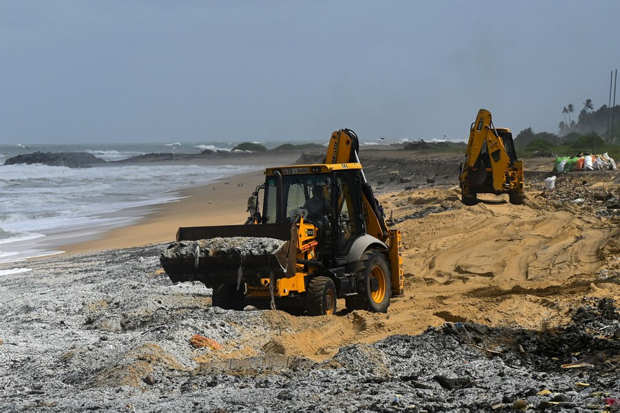 Two front-end loaders move debris and sand on a polluted beach.