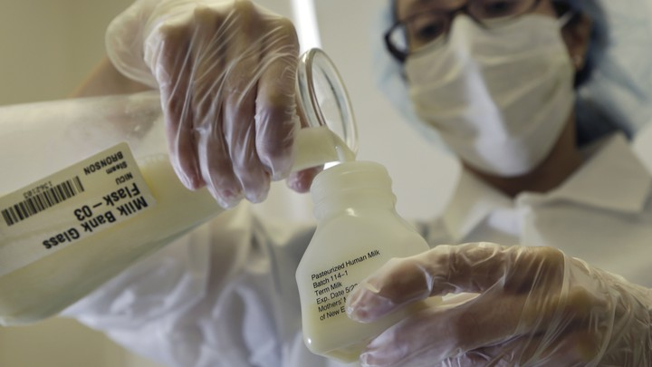 """A person wearing gloves and a surgical mask pours liquid from a flask labeled """"Milk Bank"""" into a jar"""