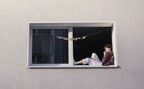 A woman lounges in the window of an apartment building