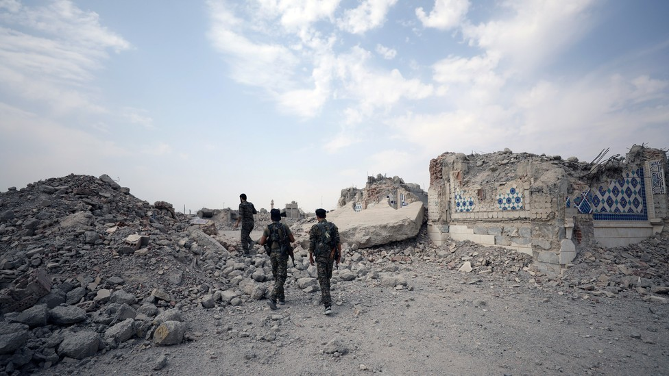 Fighters from Syrian Democratic Forces stand near the destroyed Uwais al-Qarni shrine in Raqqa, Syria.