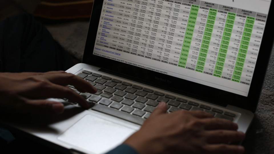 Someone's hands rest on a laptop displaying a large spreadsheet.